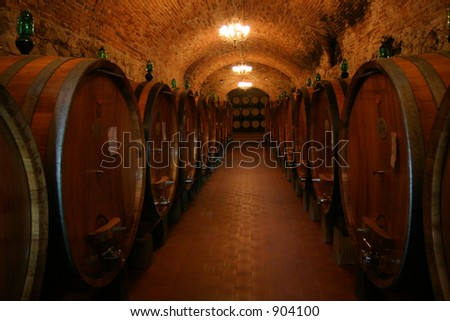 A wine cellar full of barrels of wine - stock photo