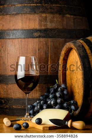 A wineglass with red wine on a wooden table with grapes and cheese