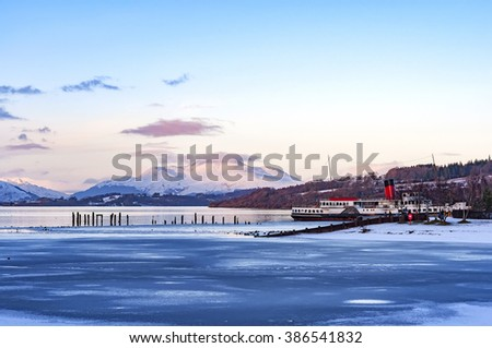 A winter view of the majestic and impressive ben lomond from across a partially frozen loch lomond near the scottish town of balloch. - stock photo