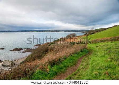A winters day on the South West Coast Path as it approaches Polkerris with Par Docks and St Austell in the far distance - stock photo