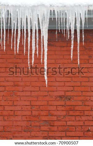 A wintry scene of long icicles hanging from a roof top edge down toward a red brick exterior wall. - stock photo