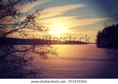 A wintry sunset. An image of a sunset on a cold winter day. Sun is going down behind a lake covered with ice and snow. Some forest is in the background. Image has a strong vintage effect applied. - stock photo
