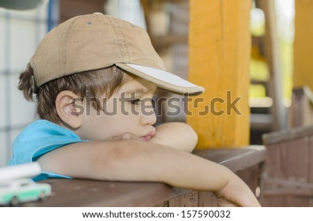 A wistful child on his porch - stock photo