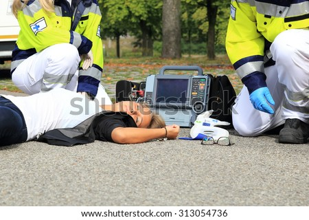 A Woman after Accident with paramedic and defibrillator first aid - stock photo