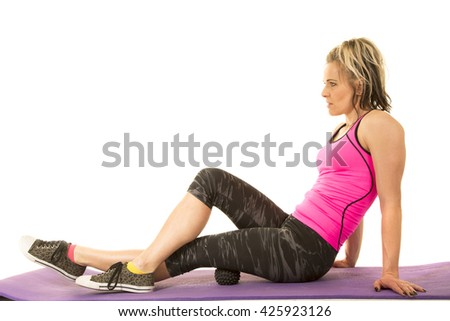 A woman after her workout rolling out on her massage ball.