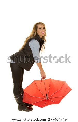 a woman all ready for the rain, bending over holding on to her umbrella.