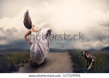 a woman and a fox on a path  - stock photo