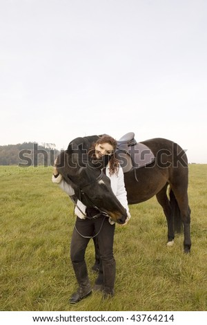 A woman and a horse stand in a field. - stock photo