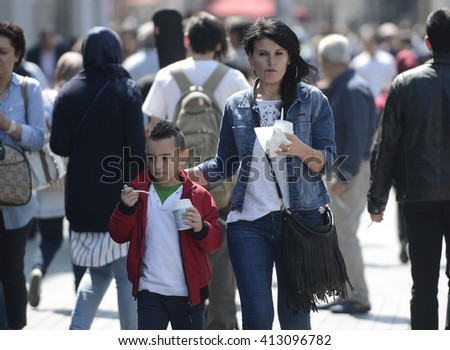 A Woman and child eating fast food while walking on Istiklal street in Istanbul, Turkey, 28 April 2016 - stock photo