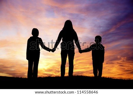 A woman and her son and daughter watch the pretty sunset. - stock photo