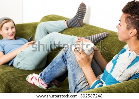 A woman and her teenage son at home, sitting on a couch talking - stock photo