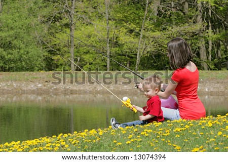a woman and her young boy child go fishing at the pond - stock photo