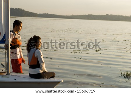 A woman and man are next to a sailboat.  They are smiling and looking away from the camera.  Horizontally framed shot. - stock photo