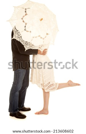 A woman and man cuddling and hiding behind the umbrella.  The woman has her foot up. - stock photo