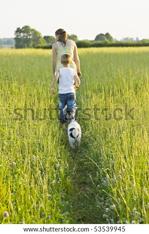 A woman and young boy out walking the dog - stock photo