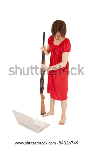 A woman angry at her computer getting ready to slam it with a gun. - stock photo