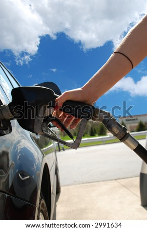 A woman at the gas pump - stock photo