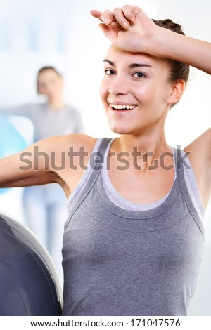 A Woman at the gym wipes the sweat from his forehead comprehensive training  .Athletic woman in the gym  - stock photo