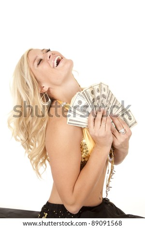 A woman being a genie holding a handful of cash with her head back laughing. - stock photo