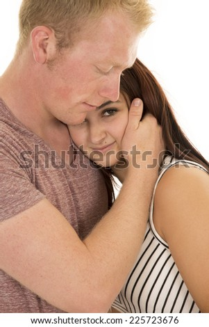 a woman being held by her man, laying her head on his chest. - stock photo