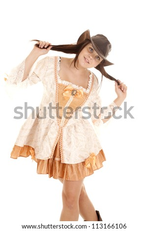 A woman being playful by playing with her hair under her cowgirl hat. - stock photo