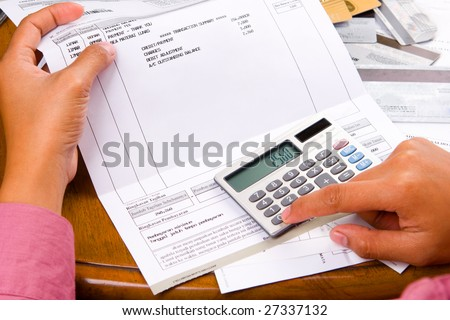 a woman calculation all the bills she have using a calculator. - stock photo