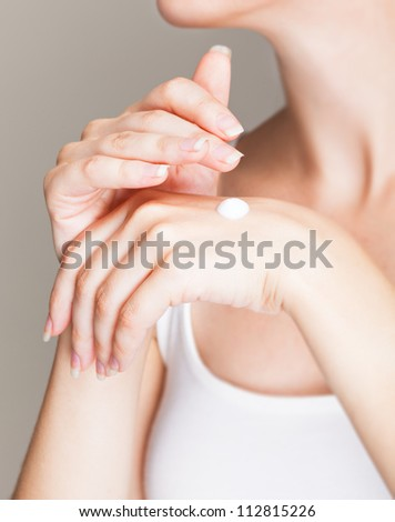 A woman cares about her hands. Isolated on a grey background