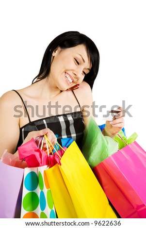 A woman carrying shopping bags and talking on the phone - stock photo