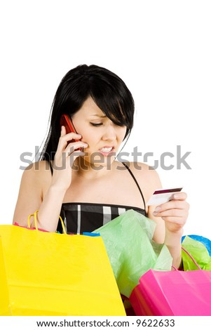 A woman carrying shopping bags calling her credit card company - stock photo