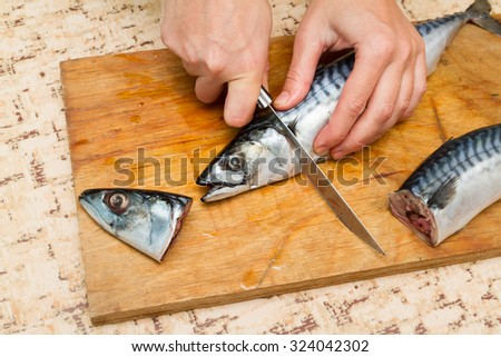 A woman chef slices a fish mackrel on a wooden Board on the kitchen table