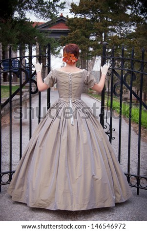 A woman clad in a 1860s gown, shown from behind, enters a wrought iron gate - stock photo