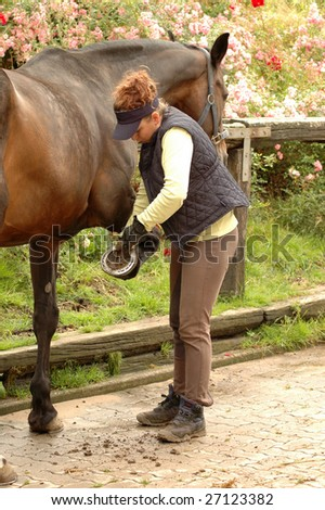 A woman cleans a horse's hoof.