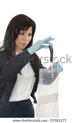 A woman collecting evidence, places a knife in a plastic bag - stock photo