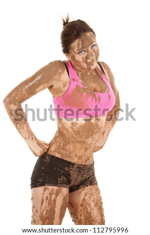 a woman covered in mud with a funny expression on her face with her hands on her hips - stock photo