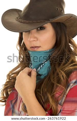 A woman cowgirl with her hand on her bandanna ready to cover her face. - stock photo