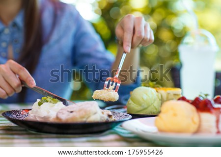 A woman cutting a piece of cake - stock photo