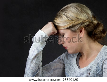 A woman deep in thought or with a headache, against a dark background room for copyspace - stock photo
