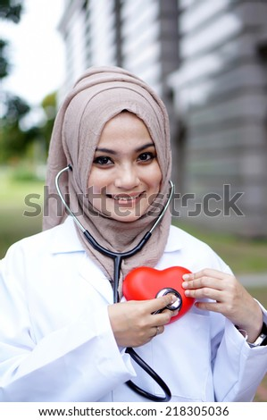 A woman doctor holding a heart symbol - stock photo