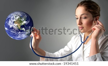 a woman doctor holding  stethoscope on a planet earth globe - stock photo