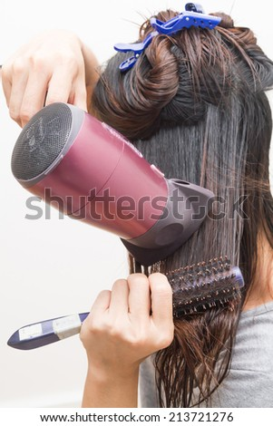 A woman doing a hair dryer and comb with herself.