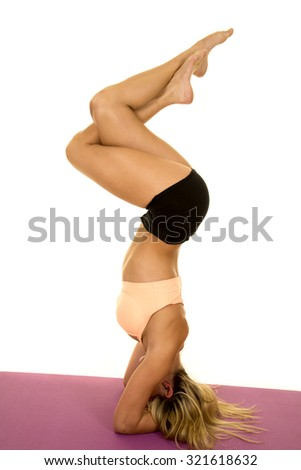 a woman doing a head stand on her fitness mat with her legs twisted. - stock photo
