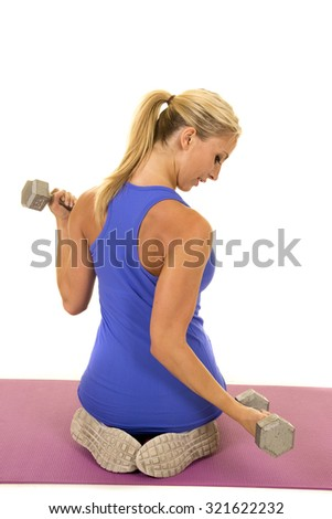 A woman doing her workout with weights kneeling down. - stock photo