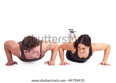 A woman doing pushups with her personal trainer - stock photo
