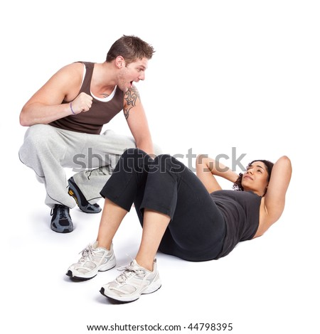 A woman doing situps with her personal trainer - stock photo