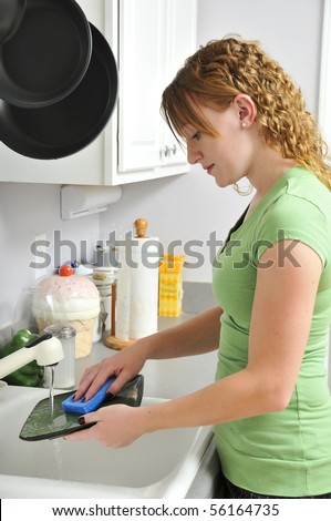 A woman doing the dishes after dinner. - stock photo