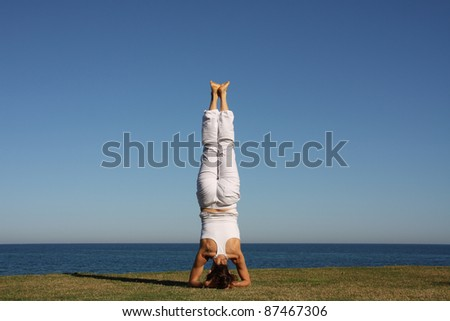 A woman doing yoga by the sea