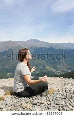 A woman doing yoga enjoying the mountain views. Side view. - stock photo