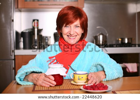 A woman drinking a cup of tea with raspberry jam - stock photo