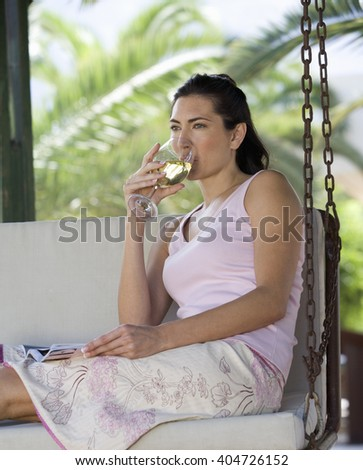 A woman drinking a glass of wine on a swing - stock photo