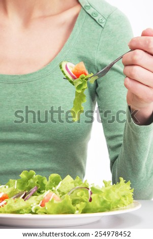 A woman eating vegetable salad, focus on the food - stock photo